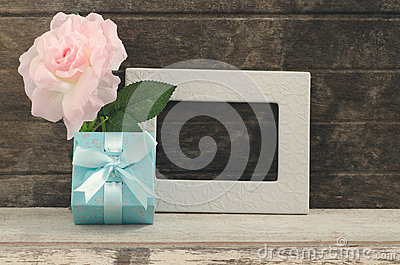 Blue gift box with blank frame and oink rose