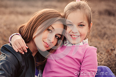 Lifestyle capture of happy mother and preteen daughter having fun outdoor. Loving family spending time together on the walk.