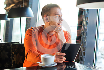 Handsome young man working with tablet,  thinking, looking out the window, while enjoying coffee in cafe