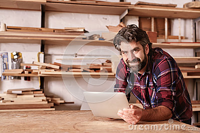 Smiling small business owner in woodwork studio with digital tab