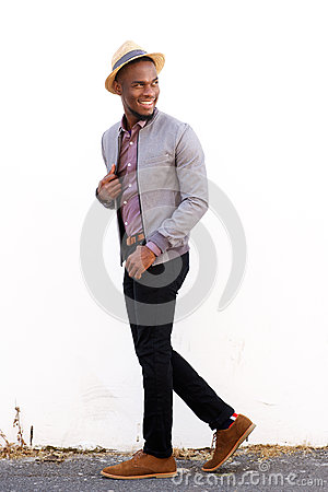 Smiling male fashion model walking and glancing back