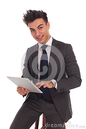 Smiling young business man touching the screen of his tablet