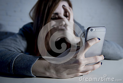 Young sad vulnerable girl using mobile phone scared and desperat