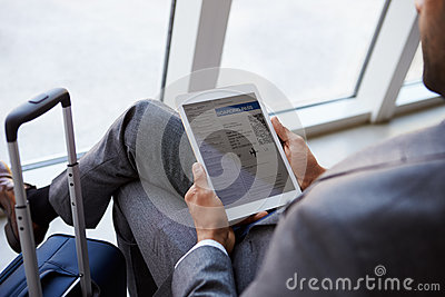 Businessman Viewing Boarding Pass In Airport Lounge