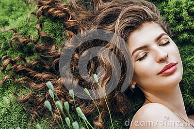 Sensual woman with long hair lying on green grass