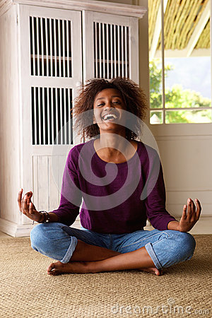 Smiling young black woman sitting on floor practising yoga