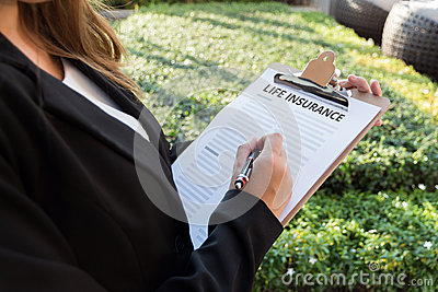 Businesswoman signing a life insurance policy on the street