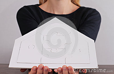 Happy family values, home insurance,real estate investment  concept. Woman holding house shape blank puzzle. Copy space image