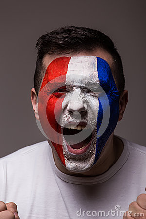 Portrait Euphoric scream of France football fan in win game of France national team on grey background.