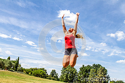 Woman jumping high to reach the sky in green park