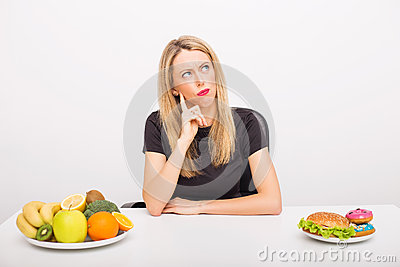 Woman deciding between healthy and unhealthy foods