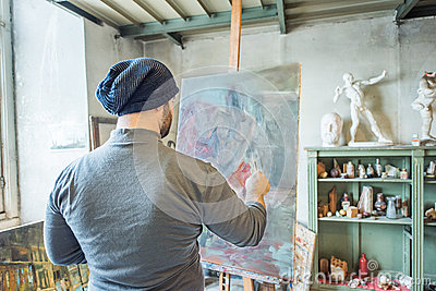 An artist painting a masterpiece at his studio