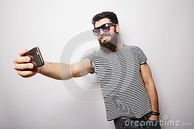 Smiling happy hipster man in sun glasses with beard taking selfie with mobile phone.