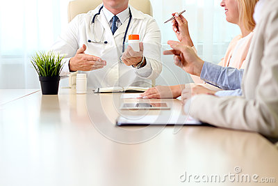 Hospital, medical education, health care, people and medicine concept - doctor showing meds to the group of happy doctors at medi