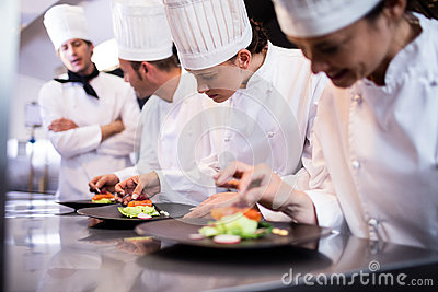 Head chef overlooking other chef preparing dish