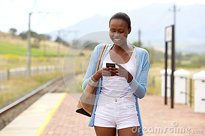 Happy african woman using mobile phone at railway station