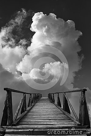 Old wooden bridge leads to unknown against sky and clouds