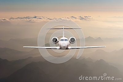 Airplane fly over clouds and Alps mountain on sunset. Front view of a big passenger or cargo aircraft, business jet