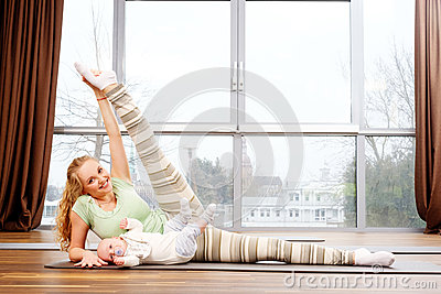 Young mother and her babie doing yoga exercises on rugs at fitness studio.