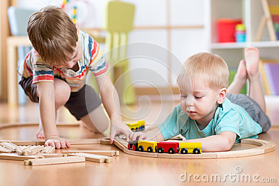 Cute children playing with wooden train. Toddler kids play with blocks and trains. Boys building toy railroad at home or