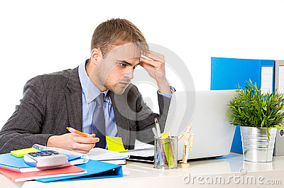Young businessman overworked looking worried sitting at office computer desk in stress