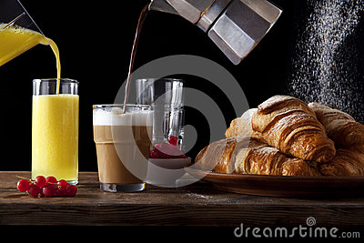 Table Breakfast. fresh hot Croissants, Pouring orange Juice, pou