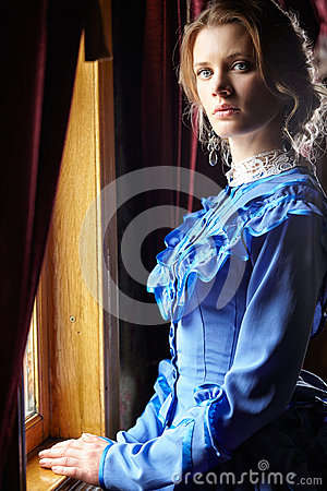 Young woman in blue vintage dress standing near window in coupe