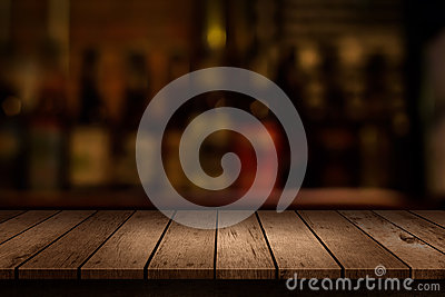 Wooden table with a view of blurred beverages bar