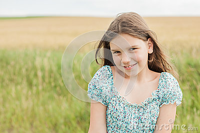 Little smiled girl on the wheat field background