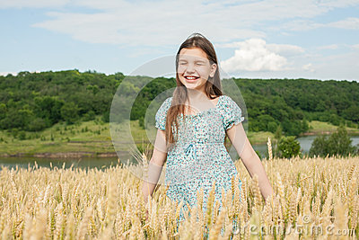 Little girl laughs on the wheat field
