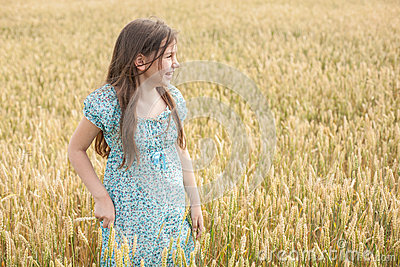 Little girl laughs on the wheat field background