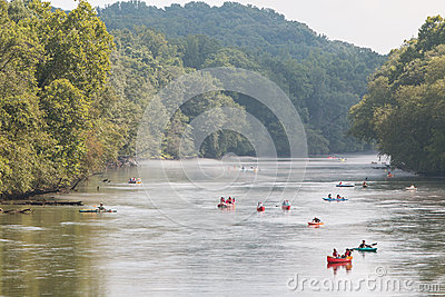 People Raft And Kayak Down River On Hot Summer Day
