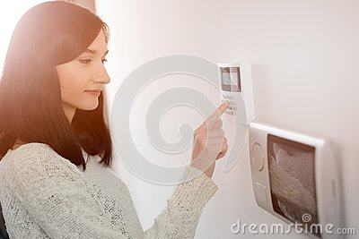 Woman entering code on keypad of home security alarm