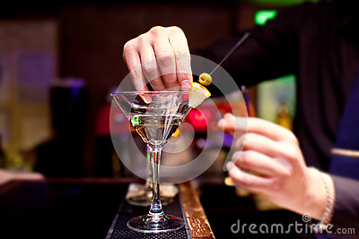 The bartender decorates stemware with martini
