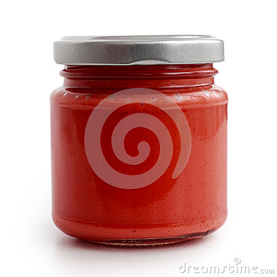 Closed glass jar of red tomato sauce.  in low perspectiv