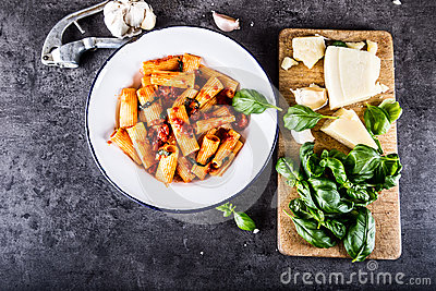 Pasta. Italian and Mediterrannean cuisine. Pasta Rigatoni with tomato sauce basil leaves garlic and parmesan cheese.
