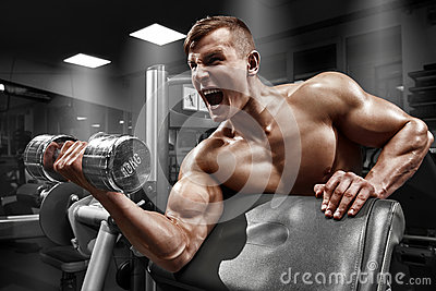 Muscular man working out in gym doing exercises with dumbbell at biceps, strong male naked torso abs
