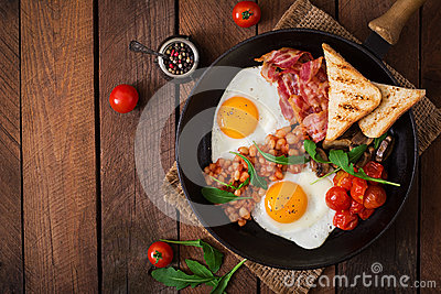English breakfast - fried egg, beans, tomatoes, mushrooms, bacon and toast.