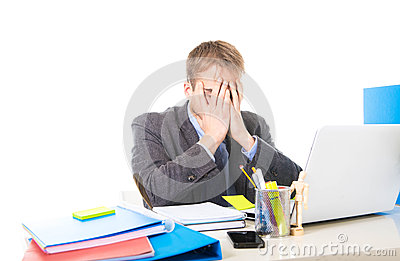 Young overworked and overwhelmed businessman covering his face suffering stress and headache
