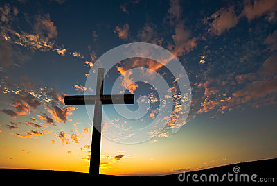 Christian cross over beautiful sunset background