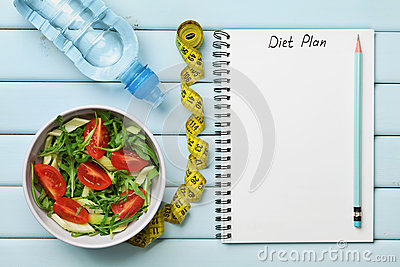 Diet plan, menu or program, tape measure, water and diet food of fresh salad on blue background, weight loss and detox concept