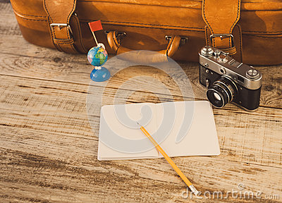 Suitcase, nootbook, pencil, flag, vintage camera on wooden planks. Aim, attainment, target, tourism, travel. At dawn. Hipster styl