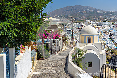 Stony road to Thira town among churches and traditional houses on Santorini island, Greece