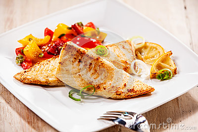 Two tilapia fish fillets on white plate