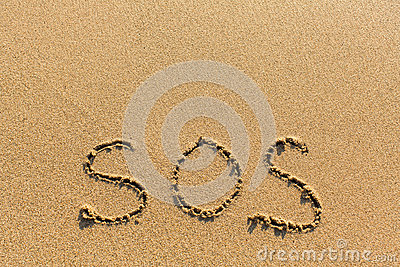 SOS - written manually on the texture of sea sand. Help.