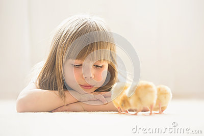 Young beautiful girl, playing with little newborn chick at home