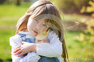 Young beautiful girl, playing with little newborn chick in the p