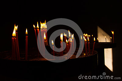Red Votive Prayer Candles Burning in Church