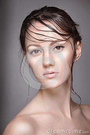 Portrait of young beautiful nude woman with wet shining  makeup on grey background