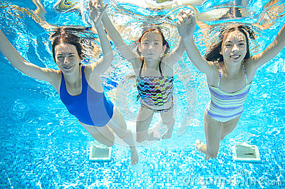 Family swims in pool under water, happy active mother and children have fun underwater, kids sport